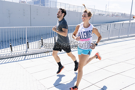 happy fit couple jogging on city
