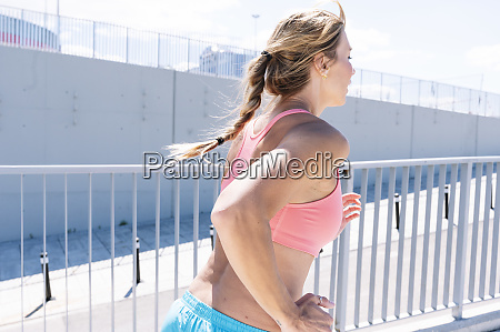 sporty woman running on city street