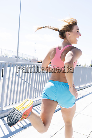 cheerful sporty woman running on city
