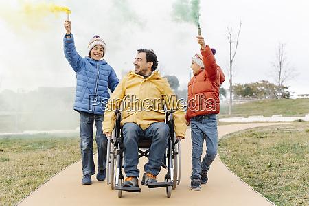 man riding wheelchair while boys walking