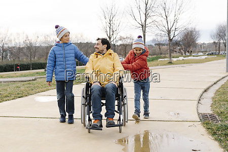 sons talking and assisting father sitting