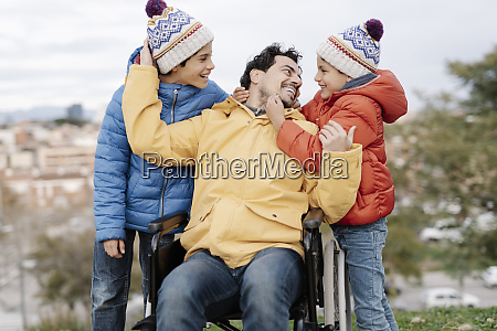 loving father embracing sons while sitting