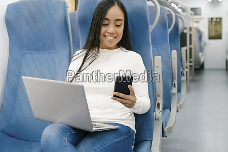 smiling woman with laptop using smart