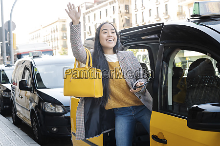 cheerful young woman waving hand while