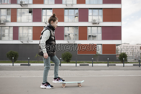 girl with skateboard standing on road