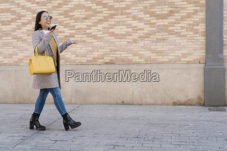stylish woman wearing sunglasses talking over