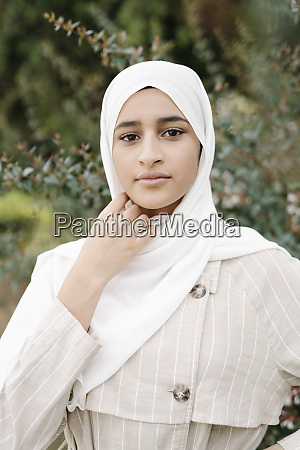 teenage girl adjusting headscarf outdoors