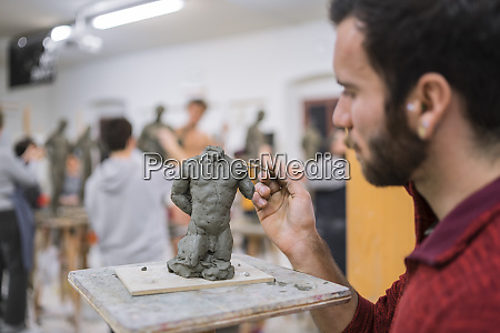 student forming sculpture