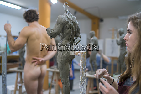 female student working at sculpture nude