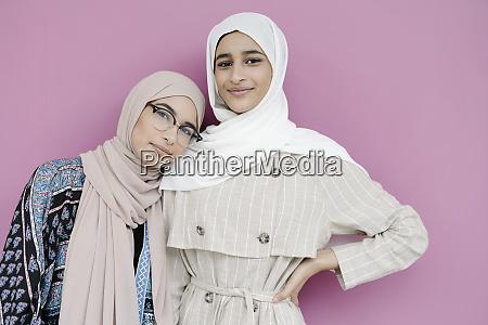 muslim sisters standing together against purple