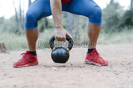 young athletic man with dumbbell in
