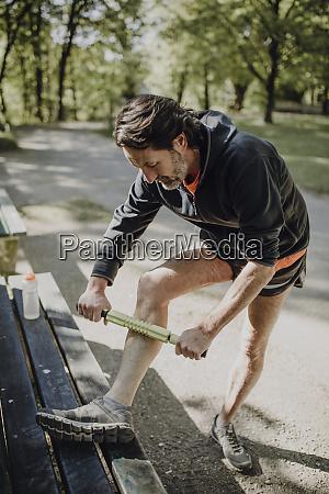 mature man massaging leg with muscle