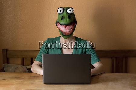 playful mature woman wearing frog mask