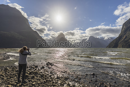 new zealand female tourist photographing scenic