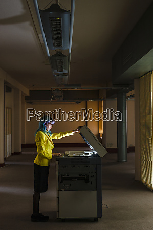 businesswoman with dyed hair operating photocopier