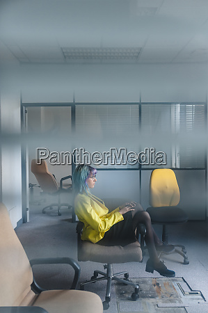 thoughtful businesswoman sitting on chair in