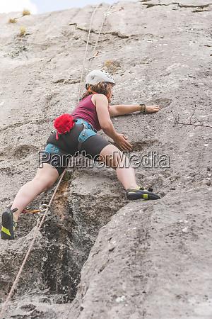 young woman climbing rock