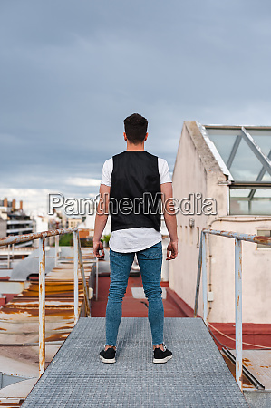 young man standing on abandoned terrace