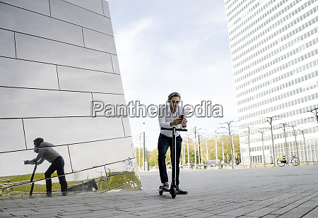 businessman with kick scooter and smartphone