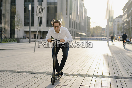 businessman riding kick scooter in the