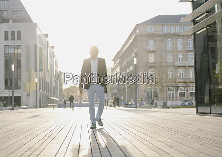 businessman walking in the city at
