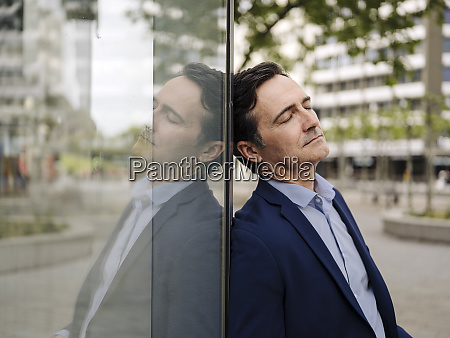 exhausted mature businessman leaning against glass