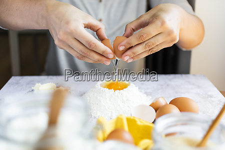 hands of woman breaking egg into