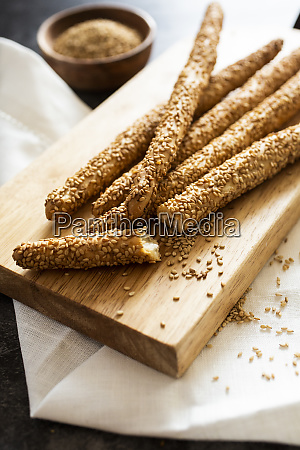 cutting board and fresh italiangrissinibreadstickswith sesame