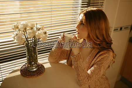 blond woman at home drinking coffe