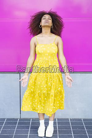 young woman wearing yellow dress meditating