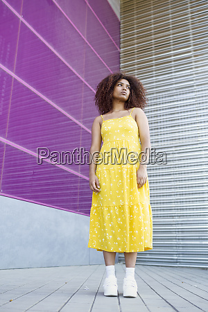 thoughtful afro woman standing on footpath