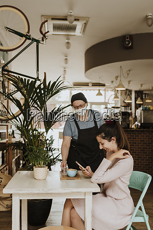 waitress with protective mask serving cappuccino