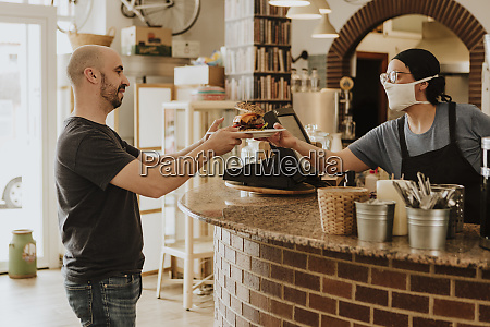 waitress with protective mask serving food
