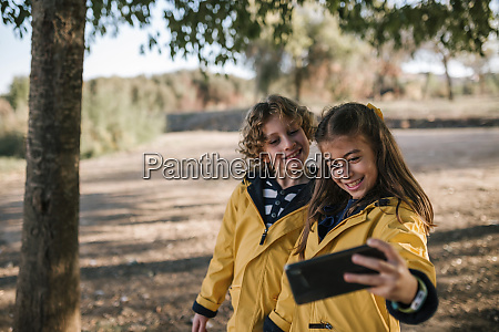 smiling girl taking selfie with brother