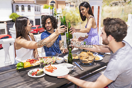 happy young friends toasting beer bottles