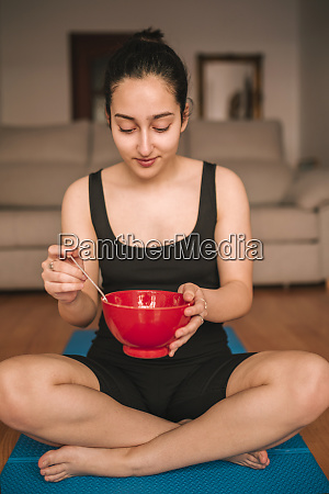 young woman holding breakfast bowl while