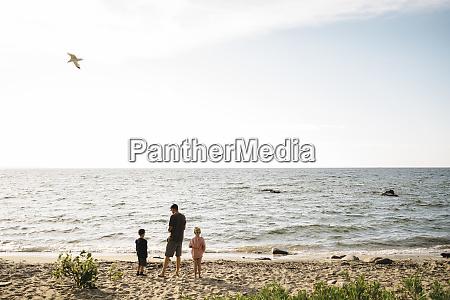 family enjoying at beach against sky