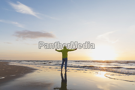 senior man with arms outstretched standing