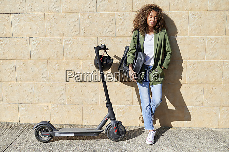 confident young woman standing with electric