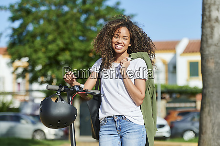 happy young woman carrying jacket while