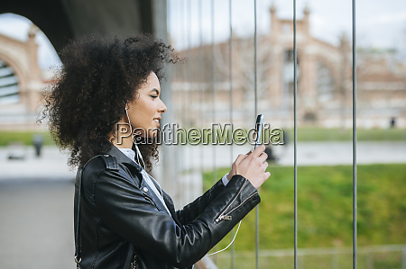 young woman with afro hairstyle photographing