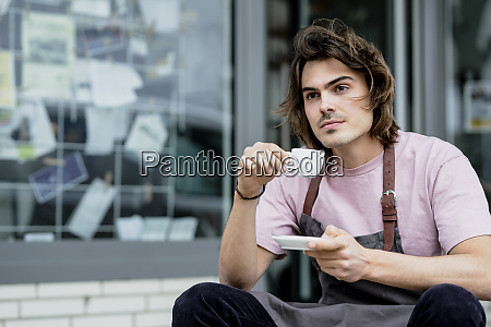 thoughtful male barista holding coffee sitting