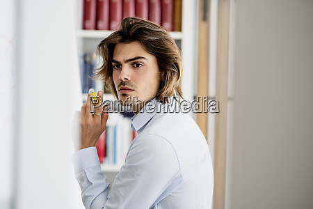 thoughtful businessman holding pen looking away