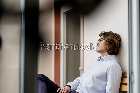 thoughtful businessman sitting on chair by