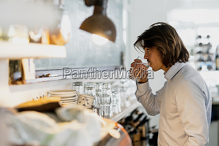 businessman drinking water while standing in