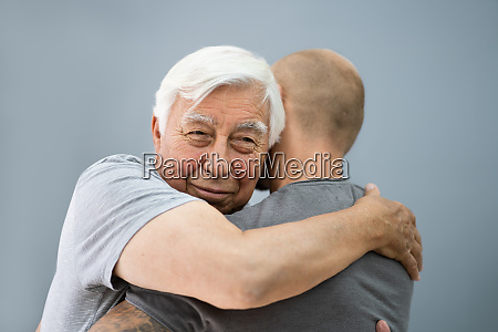 son hugging his happy grandfather
