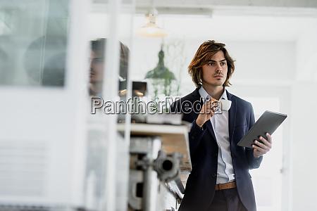 thoughtful male entrepreneur holding digital tablet