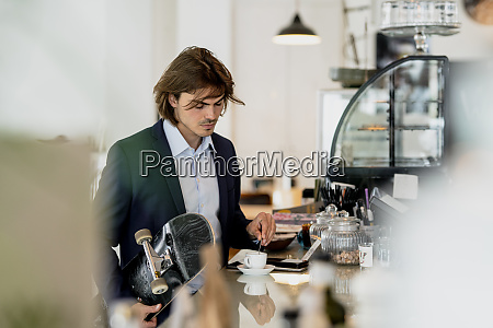 businessman holding skateboard while mixing coffee