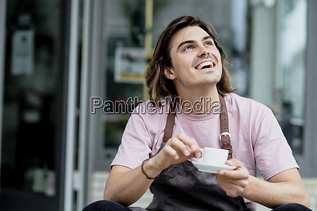 male owner holding coffee cup laughing