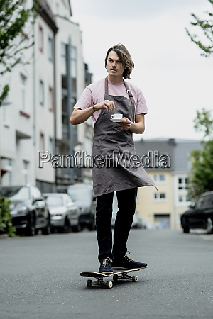 male barista holding coffee cup skateboarding